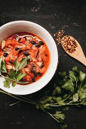 Chili aus schwarzen Bohnen und Tomaten, Holzlöffel mit Pfeffer und frischer Petersilie