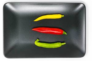 Chilipeppers in red, green and yellow on a black plate in top view