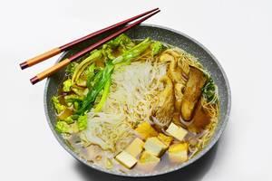 Chinesische Suppe mit Pilzen, Tofu, dünnen Nudeln und Gemüse in chinesischer Schale mit Essstäbchen