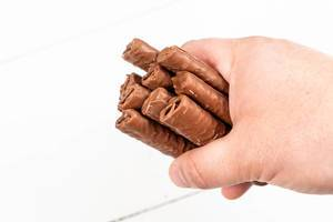 Chocolate Bars in the hand above white background (Flip 2020)