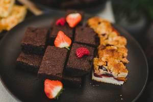 Chocolate Brownie With Berries On Black Plate