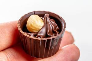 Chocolate candy with hazelnuts in a woman