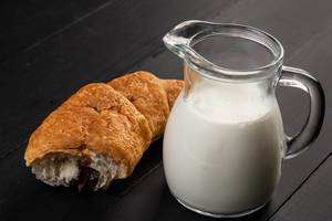 Chocolate croissant with milk on the black board