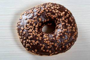 Chocolate donut on white wooden background close-up