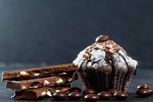 Chocolate muffin with chocolate pieces on dark background