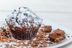 Chocolate muffin with powdered sugar and grated chocolate