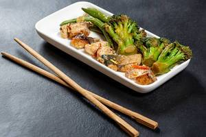 Chopsticks on black background and white plate with tuna slices and vegetables