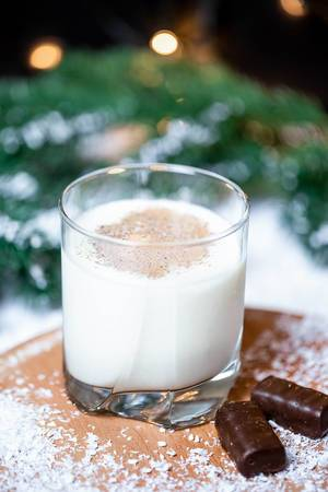 Christmas background with a glass of milk and chocolates