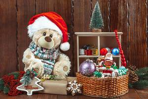 Christmas background with a teddy bear, Christmas toys and gifts on a wooden table. The concept of a children