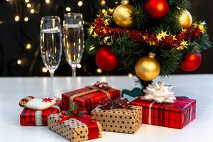 Christmas background with Christmas tree, gifts and glasses of champagne