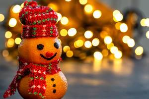 Christmas background with snowman made from tangerines and bokeh luminous garlands