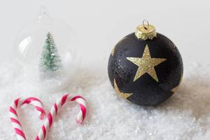 Christmas ball on snow with sugaar sticks