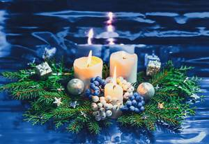 Christmas burning candles and Christmas tree branches on blue  background