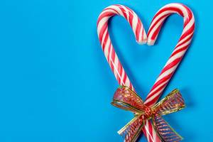 Christmas candy canes heart shaped on blue background (Flip 2019)