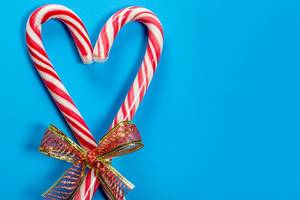 Christmas candy canes heart shaped on blue background