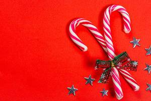 Christmas candy canes on a red background with stars