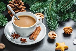 Christmas composition of coffee with gingerbread, Christmas tree branches and New Year spices on a dark background