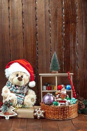 Christmas composition with a soft toy bear, Christmas toys, a Christmas tree and gifts on a wooden table. The concept of a family holiday, New Year