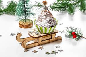 Christmas cupcake on a sled and a tree on a white background (Flip 2019)