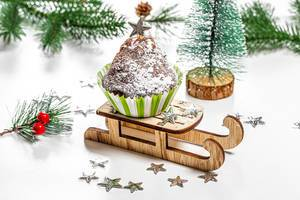Christmas cupcake on a sled and a tree on a white background