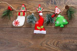 Christmas decor hanging on string on brown wooden background (Flip 2019)