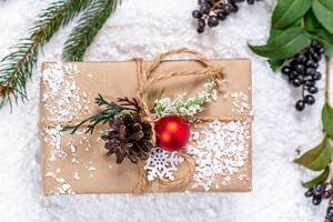 Christmas decoration: gift wrapped in beige paper with cord, a pine cone, artificial snow and a green branch