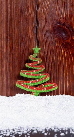 Christmas Decorations - Christmastree with snow on wooden background