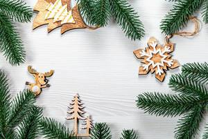 Christmas frame from wooden decorations and Christmas tree branches on a white wooden background (Flip 2019)