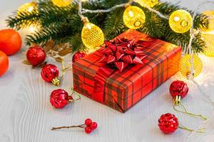 Christmas gift in red packaging with ribbon, garlands and balls