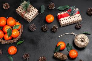 Christmas gifts with tangerines and cones on a black background. The view from the top (Flip 2019)