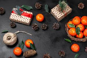 Christmas gifts with tangerines and cones on a black background. The view from the top