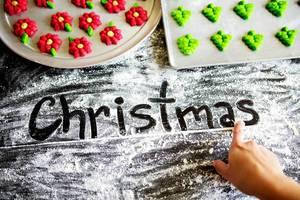 Christmas mit einem Finger in Mehl geschrieben mit Weihnachtsplätzchen