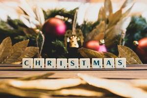CHRISTMAS mit Scrabble Buchstaben geschrieben mit Weihnachtsdekorationen im Hintergrund