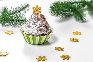 Christmas muffin with Christmas tree branches and snowflakes on a white background (Flip 2019)