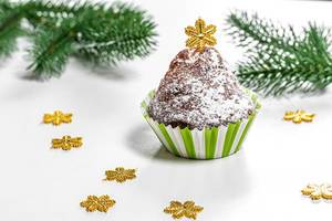 Christmas muffin with Christmas tree branches and snowflakes on a white background