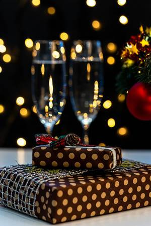 Christmas presents and glasses of champagne on bokeh background