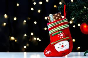 Christmas sock with a gift on a blurry background of luminous garlands (Flip 2019)