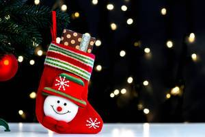 Christmas sock with a gift on a blurry background of luminous garlands