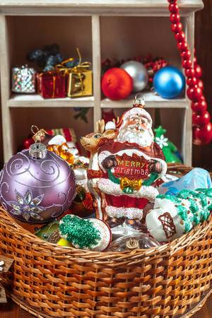 Christmas toys, balls and decor in a wicker basket. Christmas preparation for the holidays