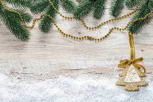 Christmas tree branches, snow and golden Christmas decor on wooden background (Flip 2019)