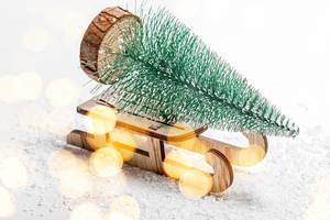 Christmas tree on a wooden sleigh on the background of snow. Christmas background with bokeh