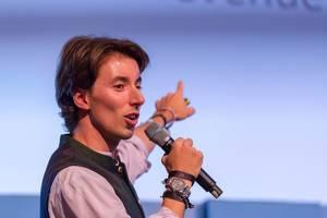 Christopher Obereder zeigt auf Leinwand während eienr Rede