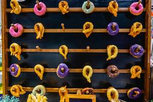 Churros and doughnuts hanging on wooden shelf