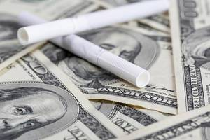 Cigarettes laying on us dollars, close up