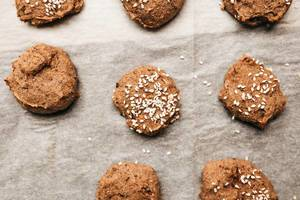 Cinnamon sesame seed sprinkled cookies on baking sheet