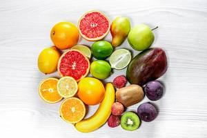 Circle of fresh fruit on white wooden background. Top view (Flip 2019)