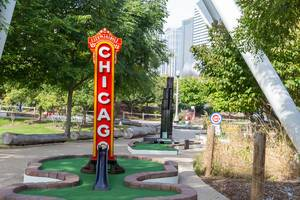 City Mini Golf in Chicago celebrating landmarks of the city, including the famous red and yellow neon sign of the Chicago Theatre and the Willis Tower