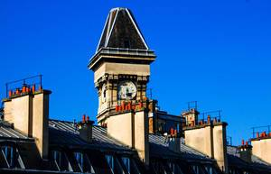 Clock on Roof of a Building in Paris