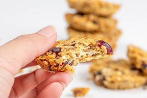 Close-up, a piece of oatmeal cookies with seeds and raisins in a woman