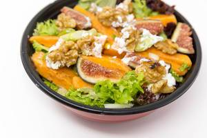 Close up -  A salat with figs, pumpkin, walnuts and cream cheese in a black bowl